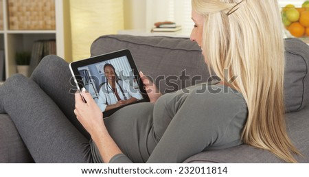 Pregnant woman talking to doctor on tablet - stock photo