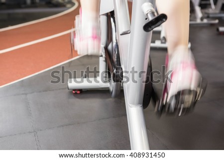 Pregnant woman using exercise bike at the gym - stock photo