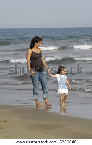 Pregnant woman walking with her child on the beach