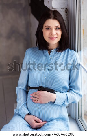 pregnant woman wearing a blue dress and sitting close to french window