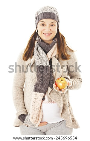Pregnant woman wearing autumn clothes eating apple. Isolated on white background  - stock photo