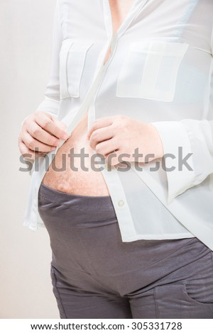 pregnant woman who tries to button up the blouse.