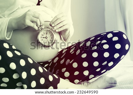 Pregnant woman with an alarm clock