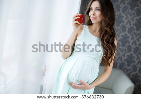 Pregnant woman with apples. Smiling pregnant woman lin bedroom.and holding apple. Beautiful young pregnant woman with apples. health care and beauty - stock photo