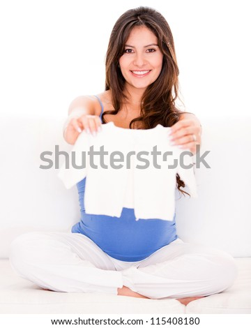 Pregnant woman with baby clothes looking very happy - stock photo