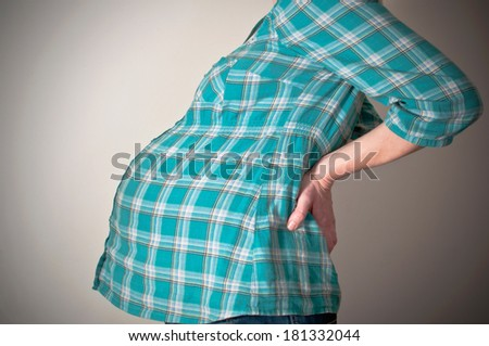 Pregnant woman with back ache - stock photo