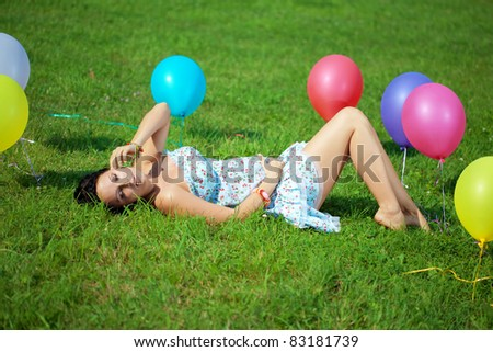 Pregnant woman with balloons in the park on grass - stock photo