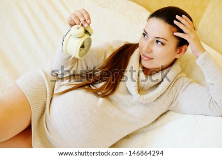 pregnant woman with clock on the sofa - stock photo