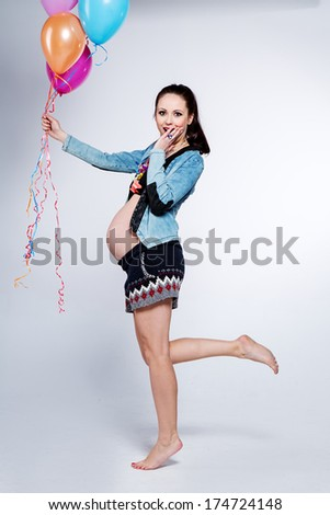 Pregnant woman with colorful balloons - stock photo