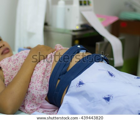 Pregnant woman with Electrocardiograph check up for her baby. hand pushing nurse call button - stock photo
