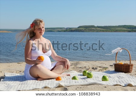 Pregnant woman with fruits sitting on the beach