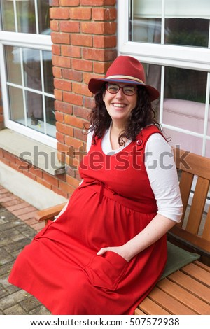 Pregnant woman with glasses wearing a red dress and hat with a big smile sitting in front of her house on a wooden bench