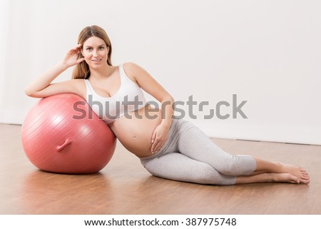 Pregnant woman with gym ball, sitting in light interior.
