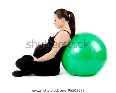 Pregnant woman with gymnastic ball. Beautiful pregnant woman sitting with exercise bal. Isolated on white background.