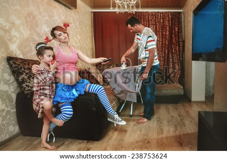 Pregnant woman with her daughter watching TV, while her husband irons a shirt  in the living room - stock photo