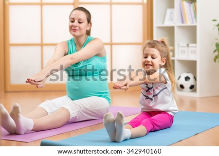 Pregnant woman with her first kid daughter doing gymnastics in living room - stock photo