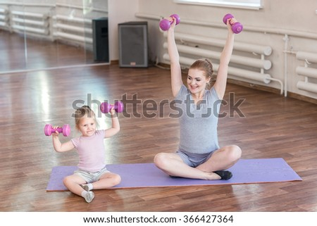 Pregnant woman with her first kid daughter doing gymnastics in living room.  - stock photo