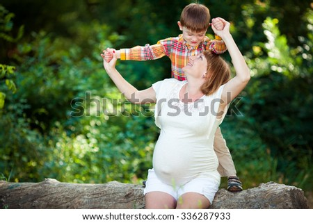 Pregnant woman with her son relaxing in park