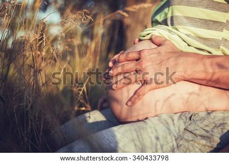 Pregnant woman with husband, holding hands on belly - stock photo