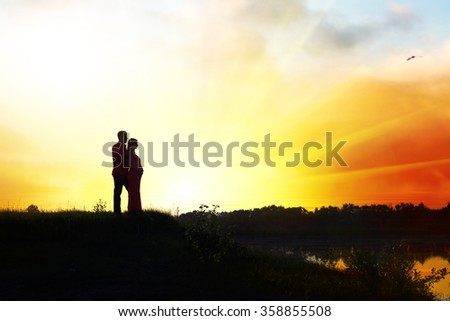 Pregnant woman with husband in sunset