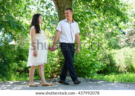 pregnant woman with husband walking in the city park, family portrait, summer season, green grass and trees - stock photo
