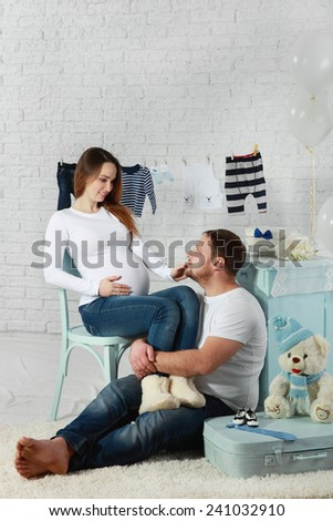 Pregnant woman with husband with child clothes - stock photo