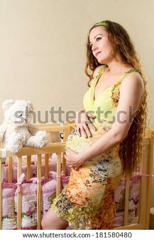 Pregnant woman with long hair with toy Teddy bear in a crib at home.  - stock photo