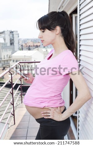 Pregnant woman with mobile phone - stock photo
