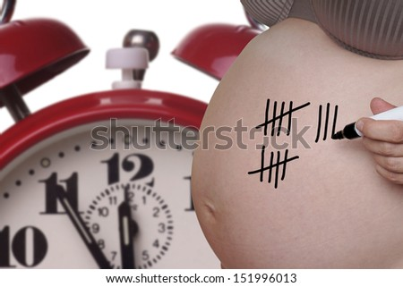 pregnant woman with pen and tally sheet on the belly / pregnancy