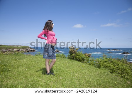 pregnant woman with pink jersey at Asturian coast - stock photo