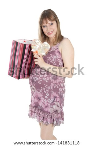 Pregnant woman with shopping bag and heart-shaped box smiling - stock photo