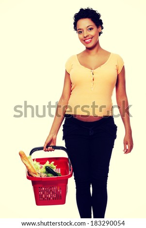 Pregnant woman with shopping basket - stock photo