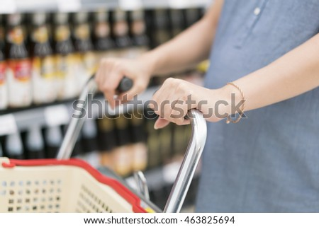 Pregnant woman with shopping cart in fresh supermarket