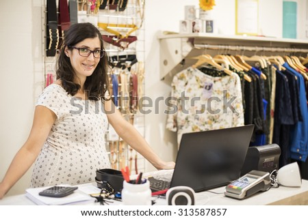 Pregnant woman working in clothes store near to computer