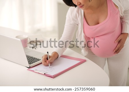 Pregnant woman writing to do list - stock photo