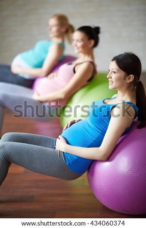 Pregnant women exercising on exercise balls in a fitness studio - stock photo