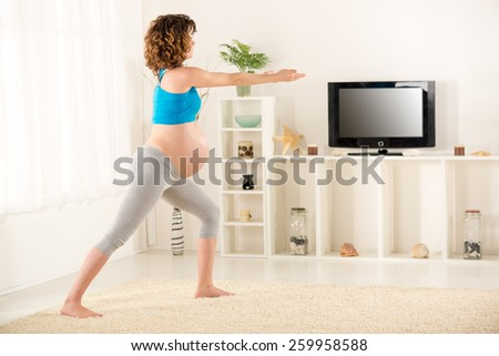 Pregnant women in sportswear, doing exercises in the living room. - stock photo