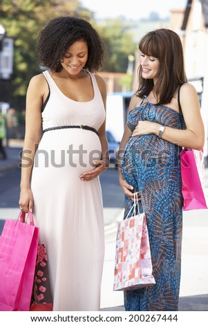 Pregnant women out shopping - stock photo