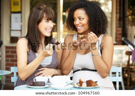 Pregnant women sitting outside caf�© - stock photo
