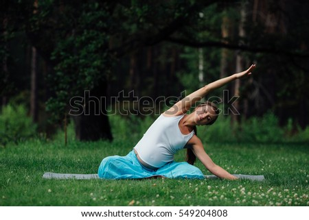 pregnant yoga in the lotus position. in the park on the grass on the mat, doing exercises, breathing, stretching, statics. outdoor, forest. concept of healthy lifestyle and relaxation. meditation.