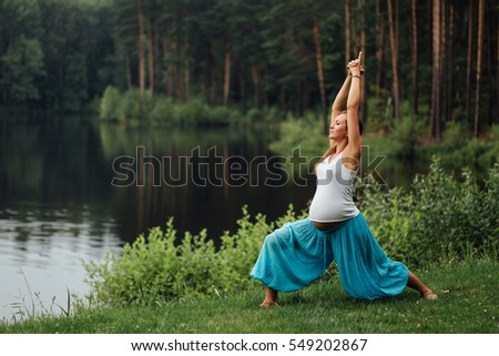pregnant yoga prenatal maternity doing different exercises. in park on the grass, breathing, stretching, statics. outdoor, forest and river. concept of healthy lifestyle and relaxation. meditation.