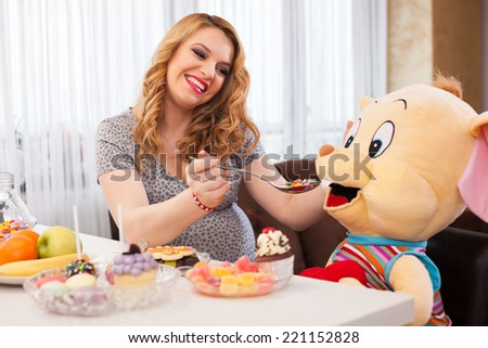 Pregnant young woman playing with a stuffed toy mouse, feeding it sweets with a spoon, sitting at the kitchen table full of sweets