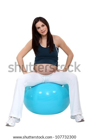 pregnant young woman sitting on inflatable balloon - stock photo