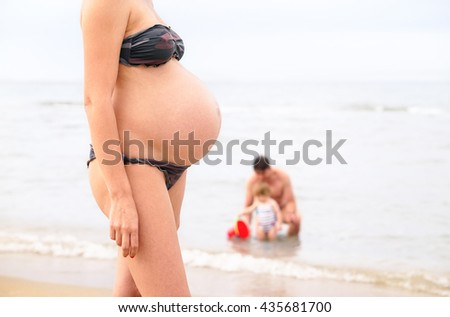 Pregnant young woman walking on beach - Mom big belly closeup with playful dad and toddler at background - Concept of family summer holidays with new baby coming soon - Soft vintage nostalgic filter - stock photo