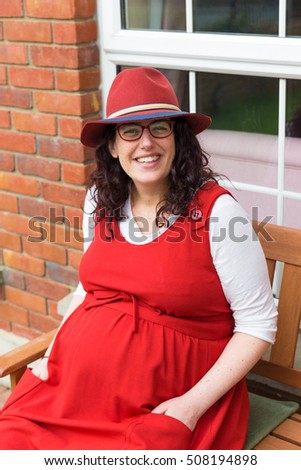 Pregnant young woman with glasses wearing a red dress and hat with a big smile sitting in front of her house on a wooden bench