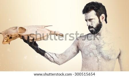 prehistoric man looking horse skull over ocher background - stock photo