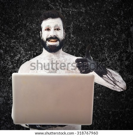 Prehistoric man with laptop - stock photo