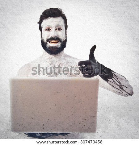 Prehistoric man with laptop over grey background - stock photo