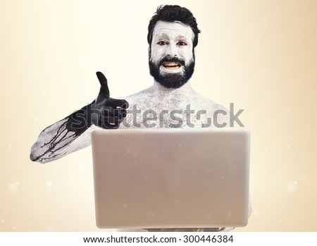 Prehistoric man with laptop over ocher background - stock photo