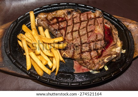 Premium American prime rib steak with french fries on a metal plate ready to serve. The focus is shallow depth of field. - stock photo